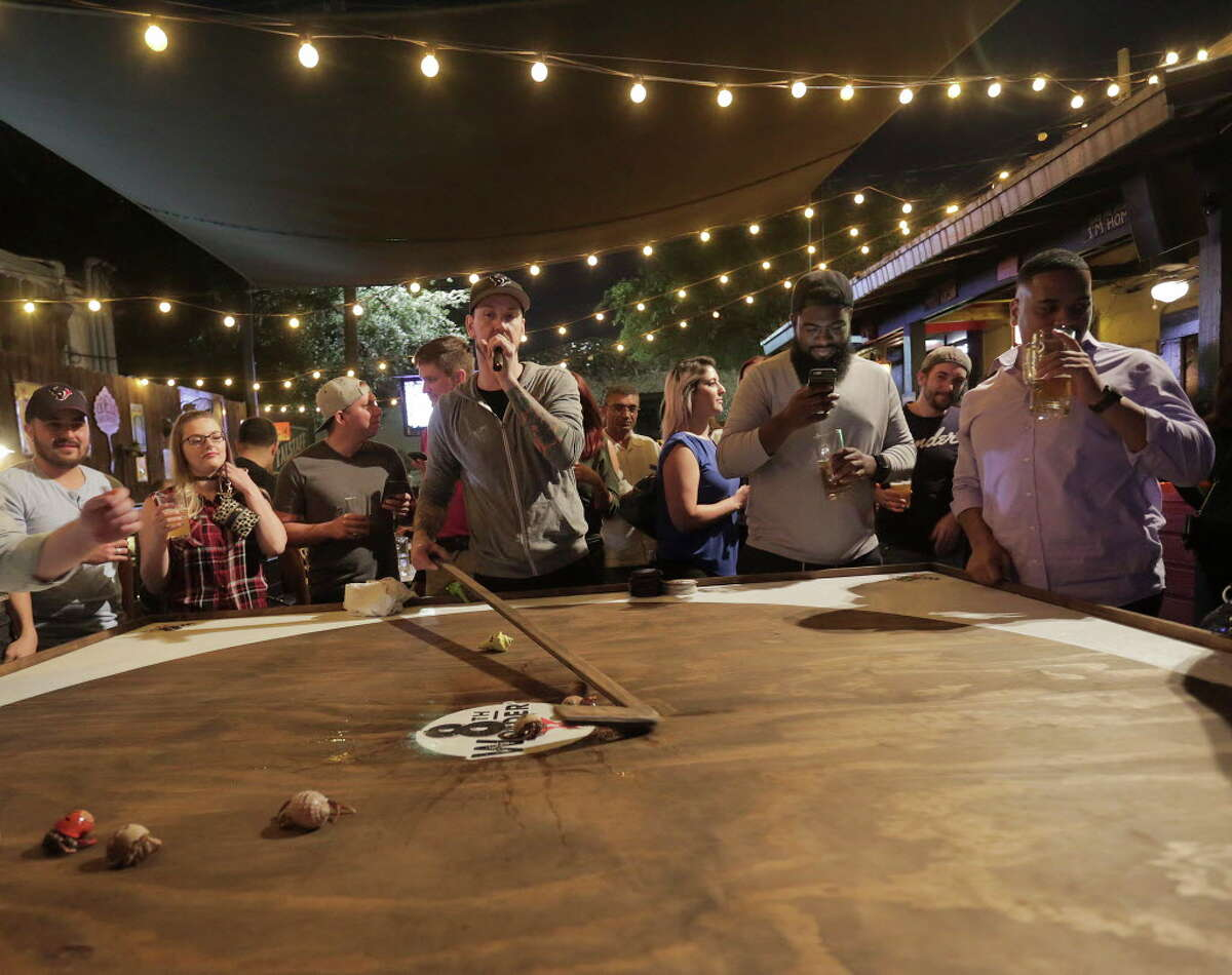 David Kemper gathers the crabs as he emcees the Hermit crab race at Little Woodrows in Eado on Tuesday, Nov. 15, 2016, in Houston.