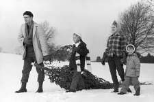 circa 1960:  A father drags a freshly cut evergreen tree through the snow for Christmas as his wife and their two daughters follow.  (Photo by Lambert/Getty Images)