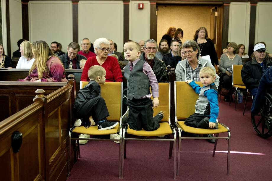 From left, brothers Devin, 4, Jaxon, 5, and Dawson, 2, look on before the start of Michigan Adoption Day on Monday at the Midland County Courthouse. Devin and Dawson's adoptions by Torie and Paul Rodgers were finalized on Monday. Photo: NICK KING | Nking@mdn.net