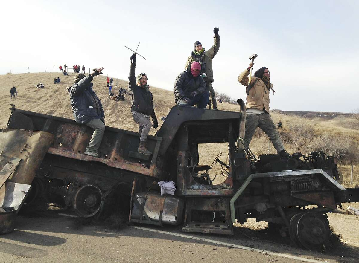 Protesters against the Dakota Access oil pipeline stand on a burned-out truck near Cannon Ball, N.D., Monday, Nov. 21, 2016, that they removed from a long-closed bridge on Sunday on a state highway near their camp in southern North Dakota. Opponents skirmished with law officers late Sunday and early Monday. (AP Photo/James MacPherson)