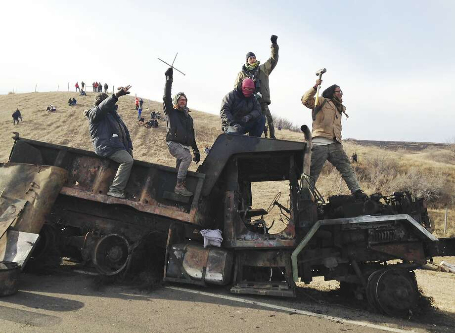 Protesters against the Dakota Access oil pipeline stand on a burned-out truck near Cannon Ball, N.D., Monday, Nov. 21, 2016, that they removed from a long-closed bridge on Sunday on a state highway near their camp in southern North Dakota. Opponents skirmished with law officers late Sunday and early Monday. (AP Photo/James MacPherson) Photo: James MacPherson, Associated Press