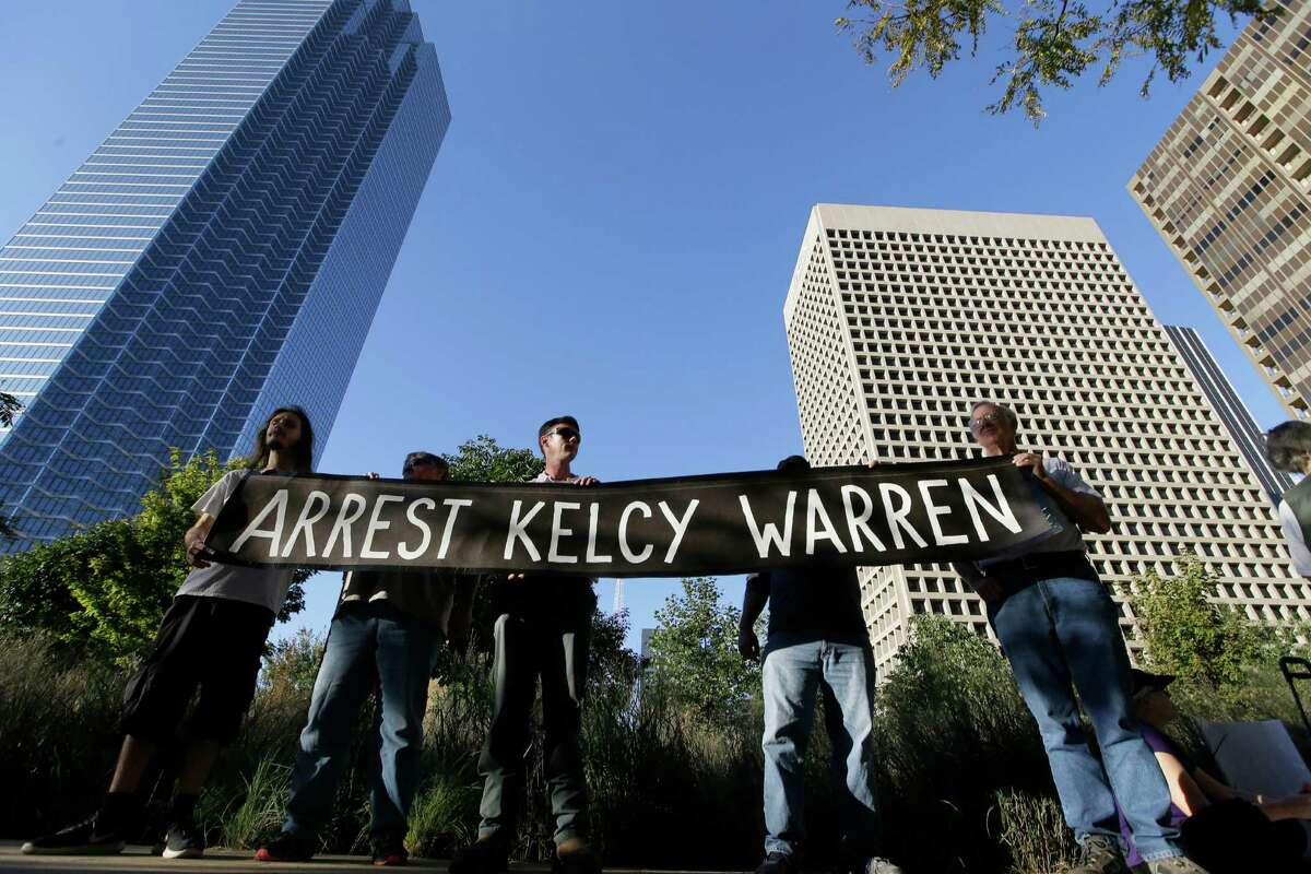 Protestors hold a sign calling for the arrest of Dallas based Energy Transfer Partners CEO Kelcy Warren during a protest outside the federal building housing the Army Corps of Engineers offices in Dallas, Tuesday, Nov. 15, 2016. People across the U.S. have gathered to show solidarity with opponents of the Dakota Access oil pipeline being built by Energy Transfer Partners. (AP Photo/LM Otero)