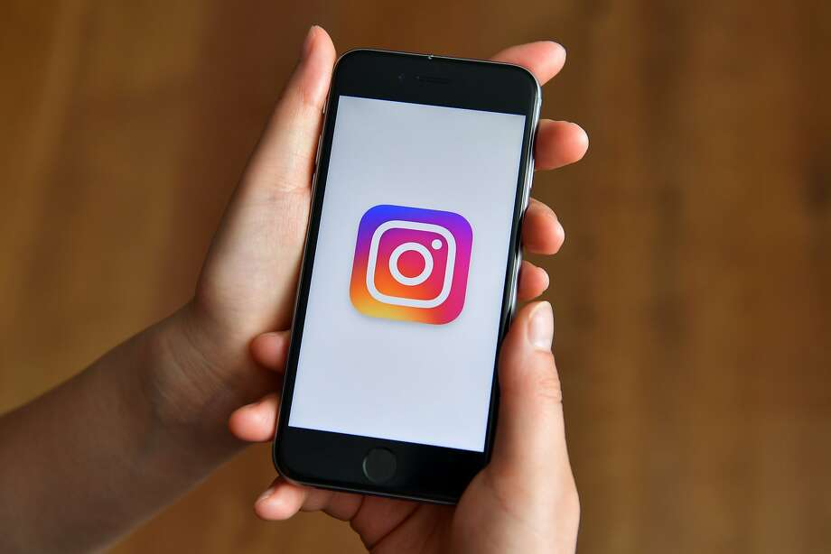 A person poses with an iPhone displaying the Instagram logo on Aug. 3, 2016. Police and school district officials in Albany are investigating allegedly racially offensive photos of African American girls at Albany High School that were posted on Instagram. Photo: Carl Court, Getty Images