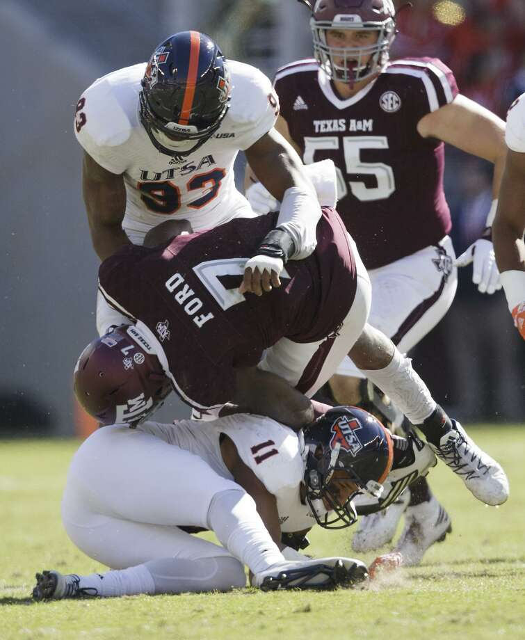 Texas A&M running back Keith Ford (7) is tackled by UTSA safety Nate Gaines (11) and defensive end Marcus Davenport (93) during the first quarter on Nov. 19, 2016, in College Station. Photo: Sam Craft /Associated Press / AP