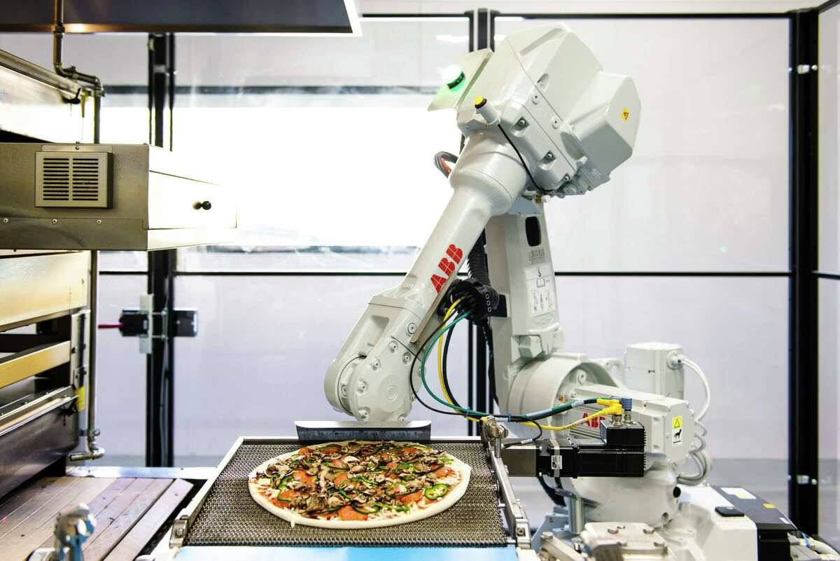 Bruno, a robotic arm, transfers a topped pie to the oven at Zume Pizza in Moutain View, Calif.