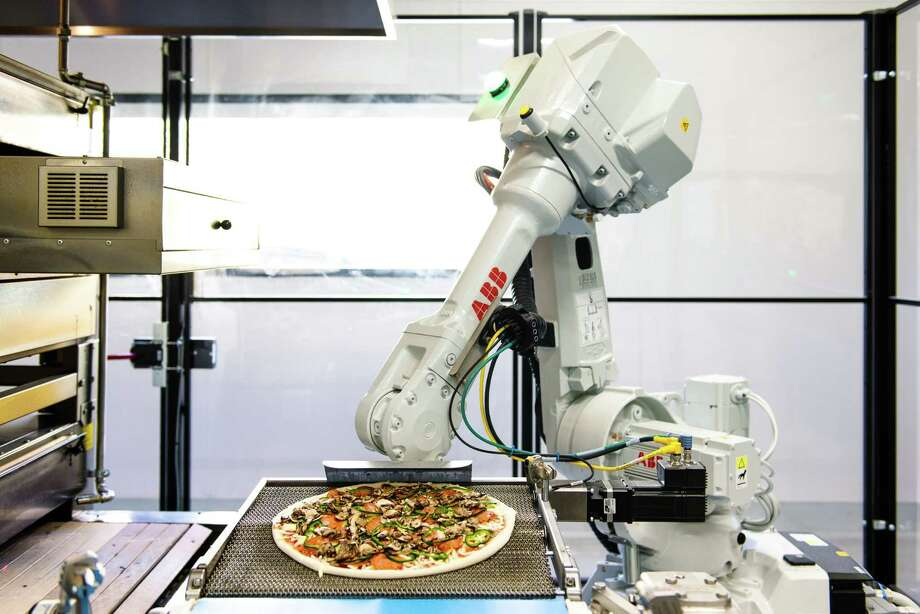 Bruno, a robotic arm, transfers a topped pie to the oven at Zume Pizza in Moutain View, Calif. Photo: Handout / Handout