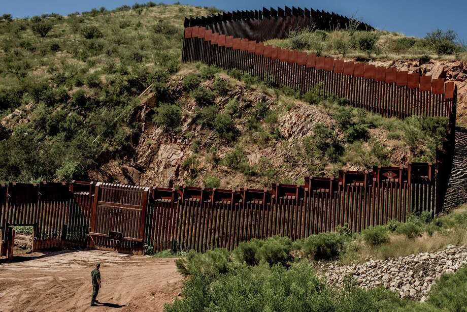 A Border Patrol agent stands at the fence along the border between United States and Mexico in the outskirts of Nogales, Ariz.. (Tomas Munita/The New York Times) Photo: TOMAS MUNITA, STR / NYTNS