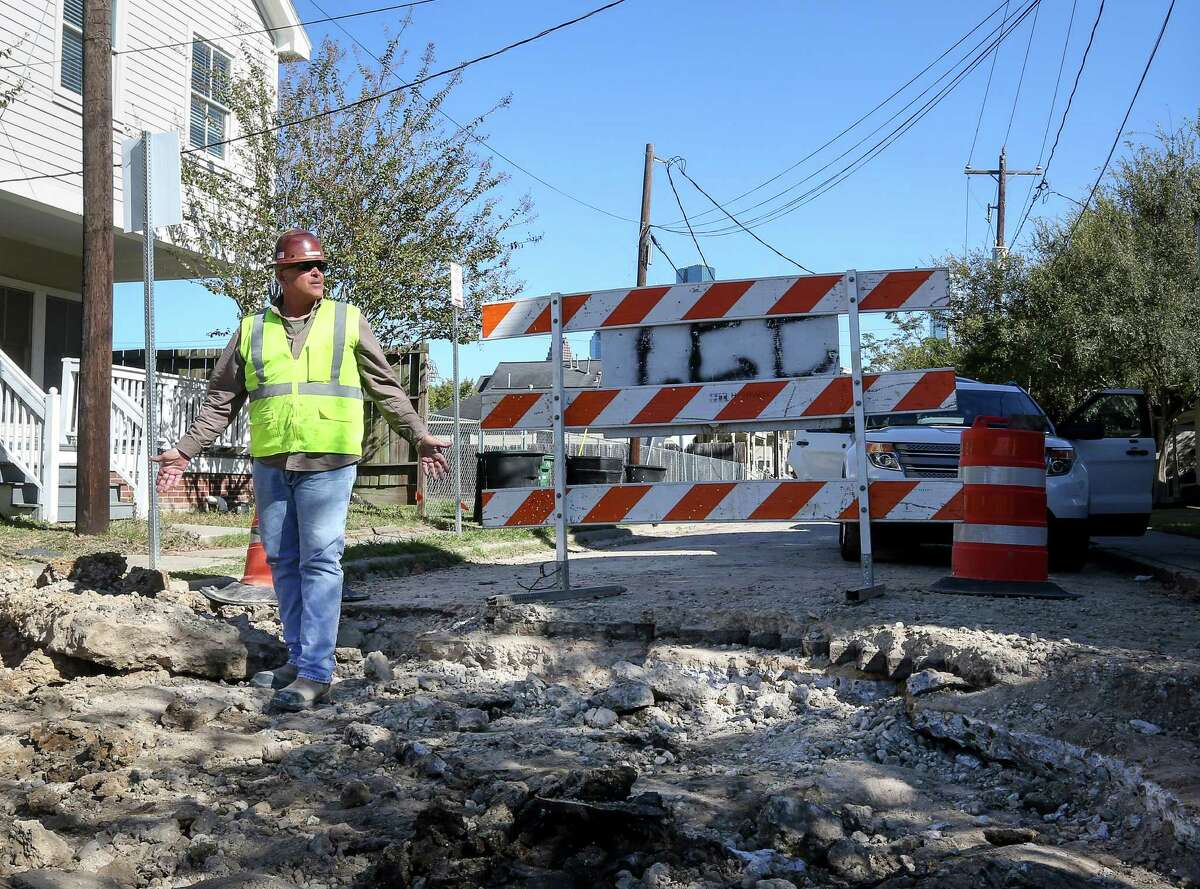 A worker inspects damage caused when a contractor dug into bricks in historic Freedmen's Town, at the corner of Genesee Street and Andrews Street on Nov. 21. The bricks were laid down by the founders of Freedmen's Town.