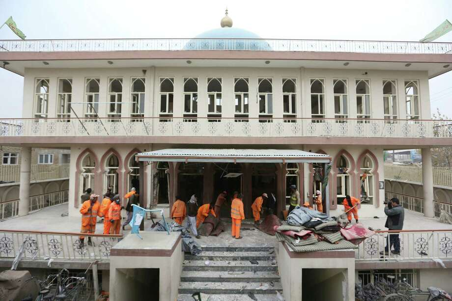 Afghan Municipality workers clear debris at the Baqir-ul Ulom mosque after a suicide bombing Monday in Kabul, Afghanistan. At least 30 people were killed, including children, and about 80 were injured. Photo: Rahmat Gul, STF / Copyright 2016 The Associated Press. All rights reserved.