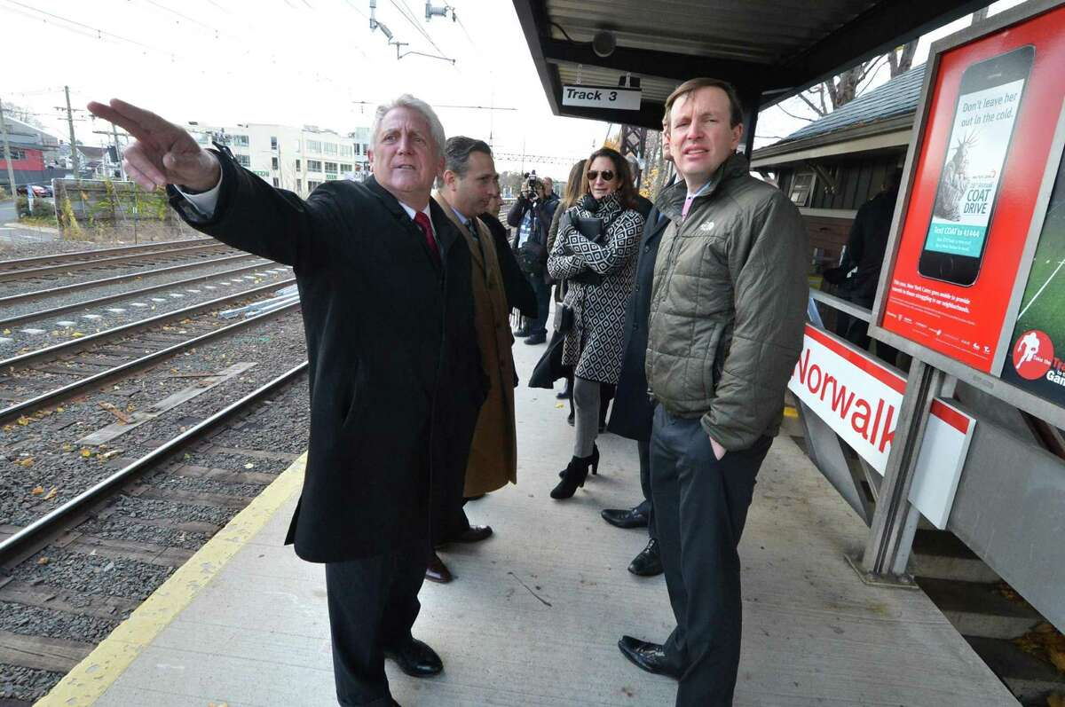 Norwalk Mayor Harry Rilling points in the direction of the eastbound Metro North tracks at the East Norwalk train station during a tour of the area in need of improvement with US Senator Chris Murphy along with State Rep Fred Wilms, State Rep Gail Lavielle and State Senator Bob Duff and other city leaders on Monday November 21, 2016 in Norwalk Conn.