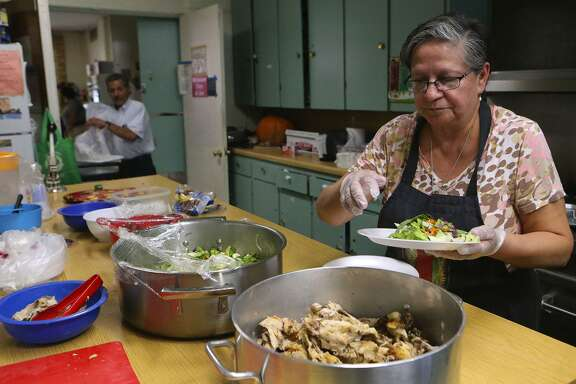 Lupita Ipina (right) assembles a fresh lunch plate at the House of Neighborly Service for local senior citizens on San Antonio's West Side. The organization distributes food to those in need three times a week and distributes boxes of food from its well-stocked pantry. It is located at 407 N. Calaveras.