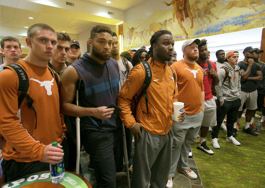 Several UT players, including from left to right, QB Shane Buechele, TE Caleb Bluiett and RB D'Onta Foreman, listen to coach Charlie Strong speak Monday. Photo: Ralph Barrera, MBO / Austin American-Statesman