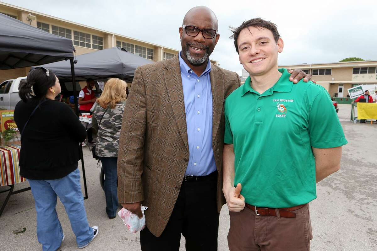 Sam Houston teacher Rick Trevinio (right) with Tony Leverett, Director of Eastside Promise Neighborhood, during the Sam Houston High School farmers market at the school on Saturday, April 18, 2015. Trevino organized the market with the help of his students. MARVIN PFEIFFER/ mpfeiffer@express-news.net