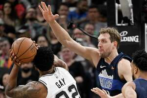 Dallas Mavericks' Dirk Nowitzki, right, defends against San Antonio Spurs' Rudy Gay during the first half of an NBA basketball game Wednesday, April 10, 2019, in San Antonio. (AP Photo/Darren Abate)