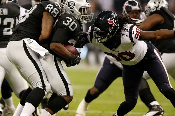 Houston Texans defensive end Jadeveon Clowney (90) tries to stop Oakland Raiders running back Jalen Richard (30) during the first half of an NFL football game at Estadio Azteca on Monday, Nov. 21, 2016, in Mexico City.