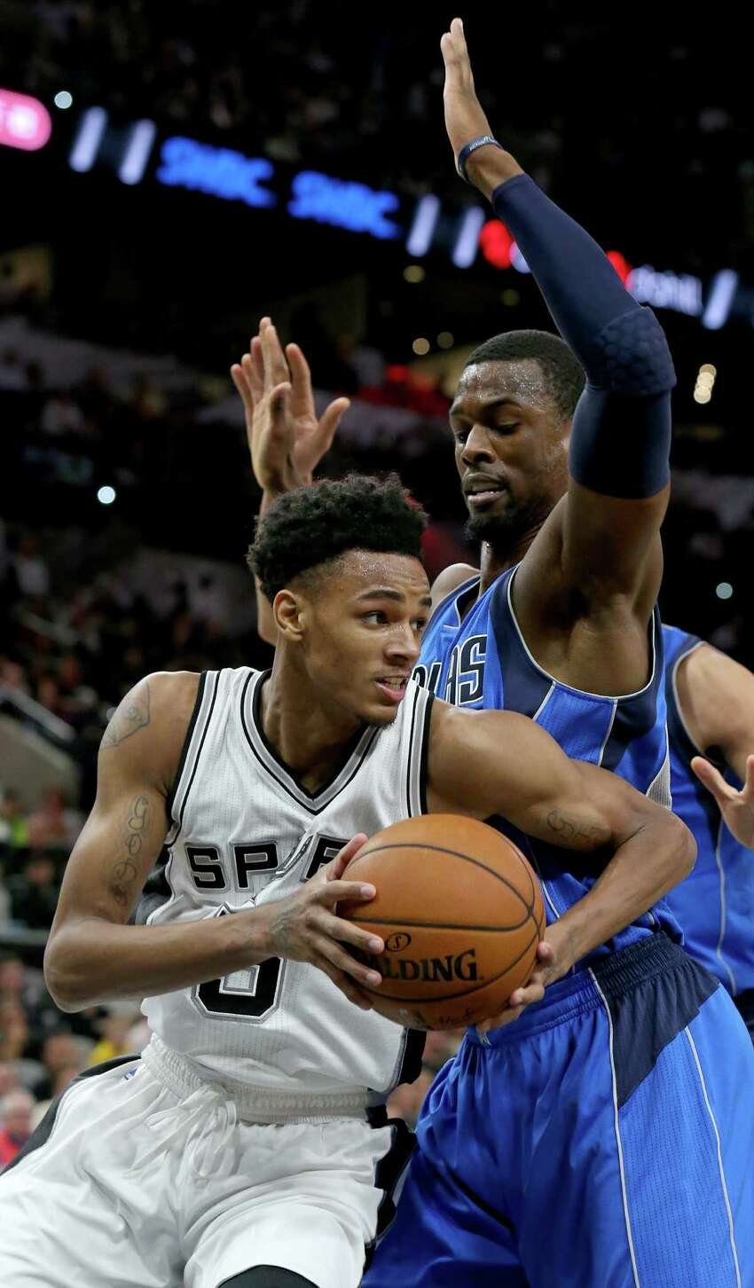 San Antonio Spurs' Dejounte Murray looks for room around Dallas Mavericks' Harrison Barnes during first half action Monday Nov. 21, 2016 at the AT&T Center.