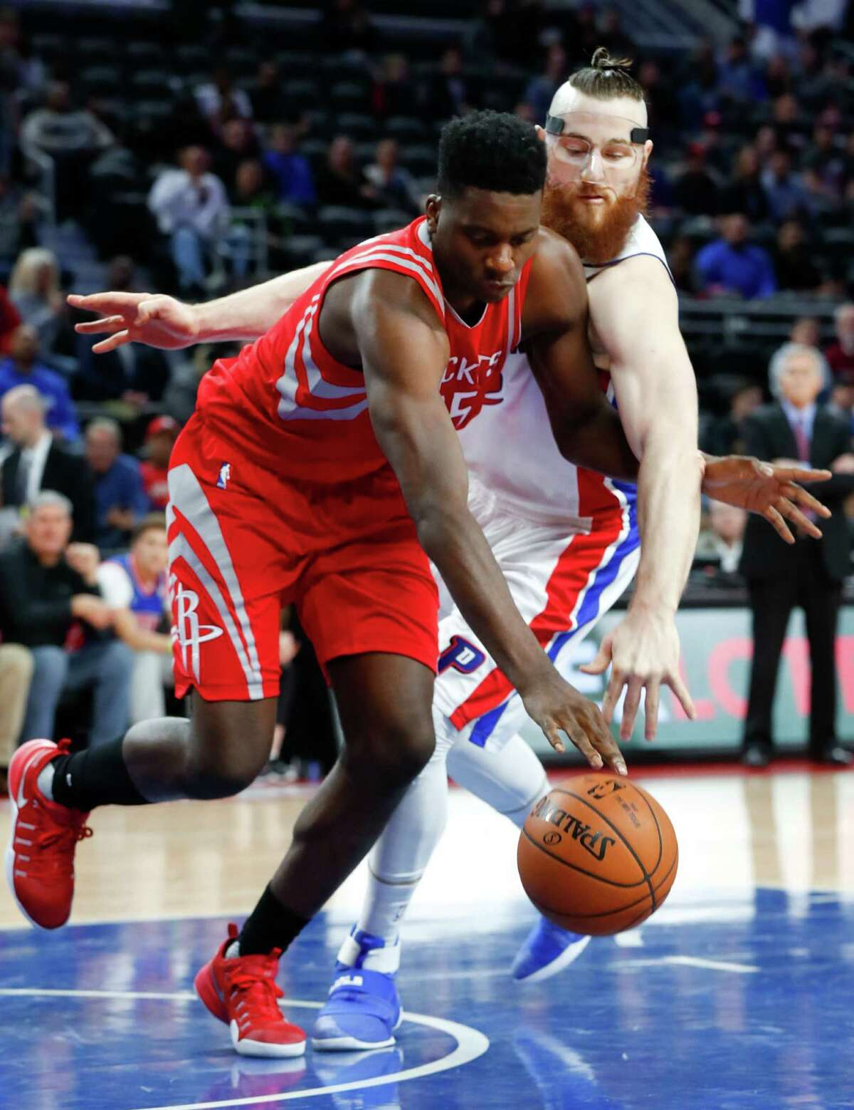 Houston Rockets center Clint Capela (15) and Detroit Pistons center Aron Baynes (12) battle for a loose ball in the second half of an NBA basketball game in Auburn Hills, Mich., Monday, Nov. 21, 2016. (AP Photo/Paul Sancya)