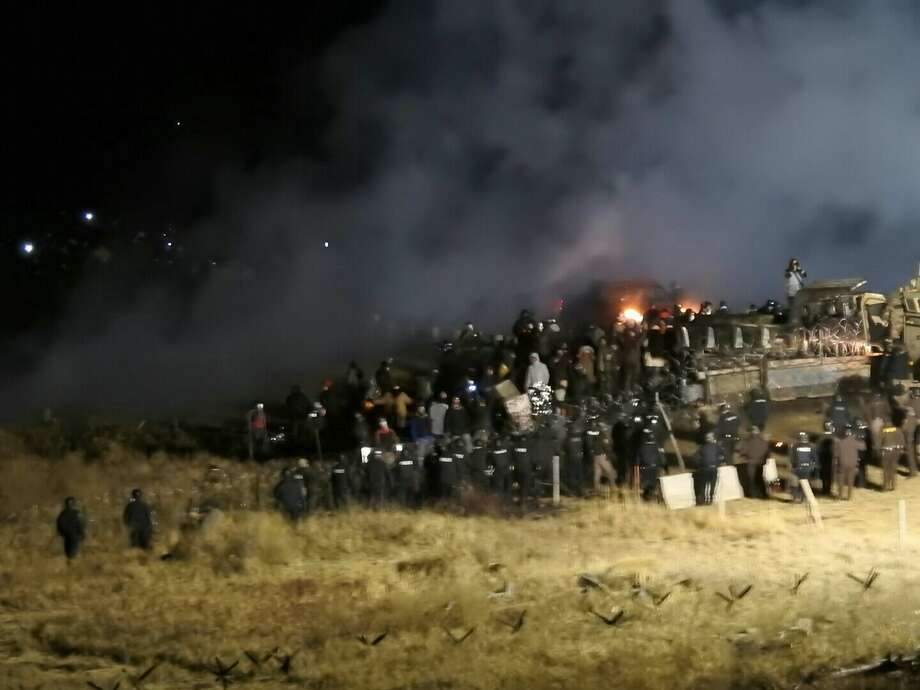 In this image provided by Morton County Sheriff's Department, law enforcement and protesters clash near the site of the Dakota Access pipeline on Sunday, Nov. 20, 2016, in Cannon Ball, N.D. At least one person arrested as protesters sought to push past a bridge on a state highway that had been blockaded since late October. (Morton County Sheriff's Department via AP) Photo: HOGP / Morton County Sheriff's Department