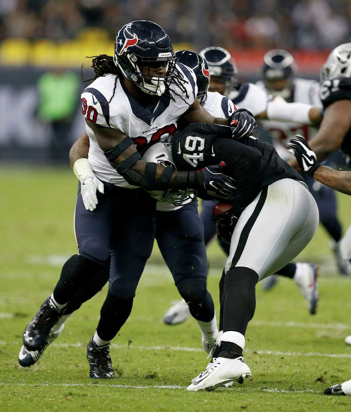 Houston Texans defensive end Jadeveon Clowney (90) wraps up Oakland Raiders fullback Jamize Olawale (49) during the second quarter of an NFL football game at Estadio Azteca on Monday, Nov. 21, 2016, in Mexico City. ( Brett Coomer / Houston Chronicle )