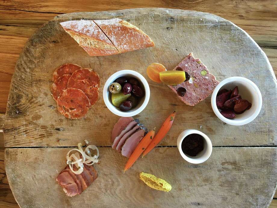 A charcuterie board with soppressata, boar tasso ham, lambs-tongue pastrami and country-style pork pate with cranberries and pistachios from Signature, Inspired by Chef Andrew Weissman Photo: Mike Sutter /Staff File Photo