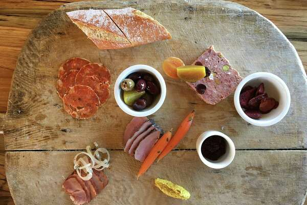 A charcuterie board with soppressata, boar tasso ham, lamb's-tongue pastrami and country-style pork pâté with cranberries and pistachios from Signature.