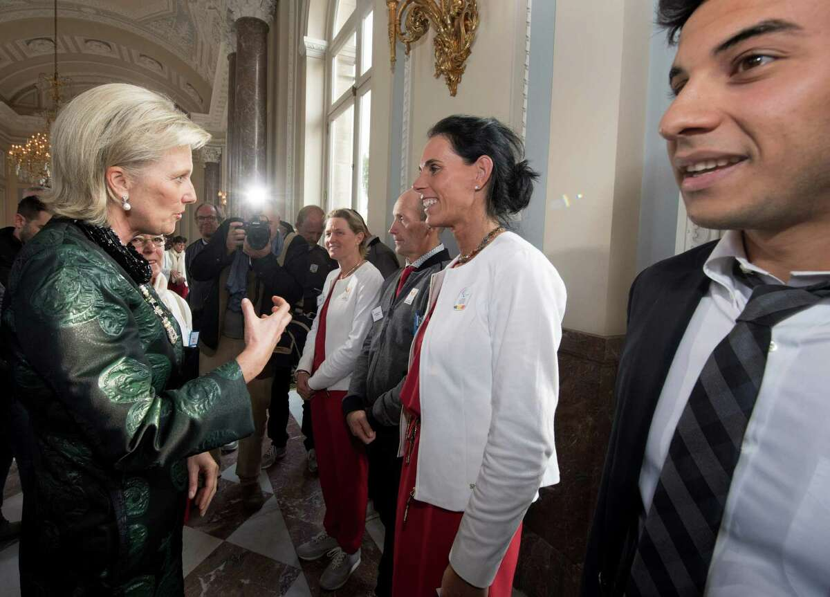 Princess Astrid of Belgium (L) speaks with Belgian jockey Michele George (C) and Syrian swimmer and refugee in Belgium Rami Anis (R) during a reception gathering athletes who competed this year, including athletes who took part in the Rio olympic games and paralympic games, on October 26, 2016, at the Royal Palace in Brussels. / AFP PHOTO / BELGA / BENOIT DOPPAGNE / Belgium OUTBENOIT DOPPAGNE/AFP/Getty Images