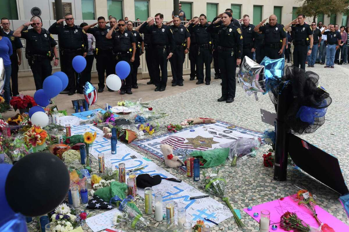 Bexar County Sheriff's Office deputies and personnel salute at the makeshift memorial for slain San Antonio Police Department Detective Benjamin Marconi in front of police headquarters on Nov. 22, 2016. Stea Rep. Jason Villalba, R-Dallas, introduced a house bill on Nov. 21, 2016, that would make it a hate crime to target police officers, firefighters and medical first responders.