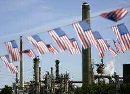 """In this April 30, 2008 file photo, American flags are seen near the Shell refinery, in Martinez, Calif. On Weds., Nov. 14, 2012, California�s largest greenhouse gas emitters will for the first time begin buying permits in a landmark """"cap-and-trade"""" system meant to control emissions of heat-trapping gases and spur investment in clean technologies. The program is a key part of California�s 2006 climate-change law, AB32, a suite of regulations that dictate standards for cleaner-burning fuels, more efficient automobiles and increased use of renewable energy. (AP Photo/Ben Margot, File)"""