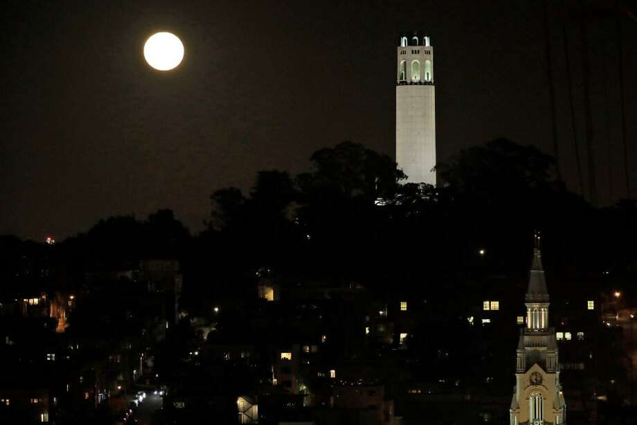 The moon rises over Coit Tower, at right, in San Francisco, Monday, Nov. 14, 2016. Nine men robbed a 31-year-old man at gunpoint at the tower's vista point early Tuesday, police said. Photo: AP Photo/Marcio Jose Sanchez / /