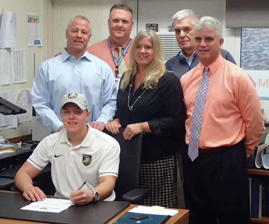 Danbury High School senior Mike Halas, front, signs his National Letter of Intent to play baseball at West Point during a ceremony at the high school on Nov. 15, 2016. Standing behind are his parents Mike, left, and Laura, third from left; along with Danbury High School Principal Dan Donovan, second from left; Danbury High School Athletic Director Chip Salvestrini, second from right; and Danbury High baseball coach Shaun Ratchford, right. Photo: Richard Gregory / Richard Gregory