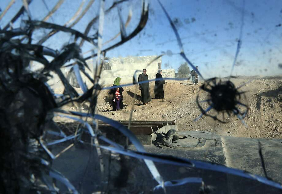 Residents walk near the bullet-riddled windshield of an Iraqi Special Forces vehicle in a Mosul. Photo: THOMAS COEX, AFP/Getty Images