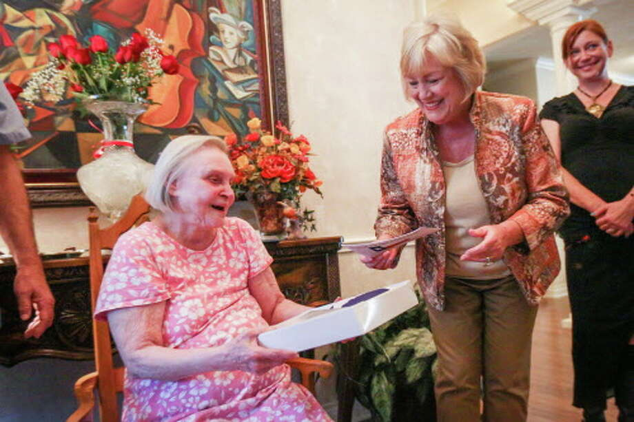 Mary Ann Metcalf mother of Rep. Will Metcalf (R-Texas), right, presents a flag that flew over the state of Texas to Lillian Niederhofer during a party in honor of her generosity and assistance to numerous local arts entities on Saturday, Nov. 19, at her home in Conroe. Photo: Michael Minasi, Staff / © 2016 Houston Chronicle