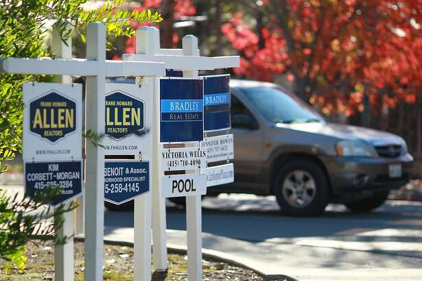 LARKSPUR, CA - NOVEMBER 30: (FILE PHOTO) A row of for sale signs are posted at the entrance to a housing complex on November 30, 2011 in Larkspur, California. The Commerce Department announced that home sales unexpectedly fell in December for the first time since August, January 26, 2012.  (Photo by Justin Sullivan/Getty Images)