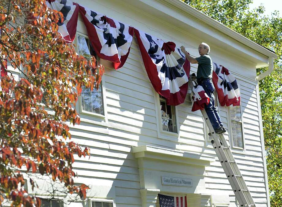 Michael Bird puts up American Flag bunting at the Gunn Memorial Historical Society and Museum in Washington, in October. Photo: Carol Kaliff / Hearst Connecticut Media / The News-Times