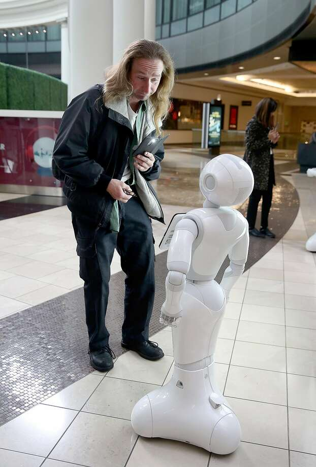 Paul Bartholomew interacts with the robot Pepper at the Westfield SF Centre on Tuesday in San Francisco. Photo: Liz Hafalia, The Chronicle