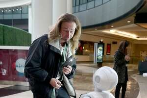 Paul Bartholomew interacts with Pepper, a robot by SoftBank Robotics, which will greet and play games with customers shopping at Westfield SF Centre during a three month pilot on Tuesday, November 22, 2016, in San Francisco, Calif.