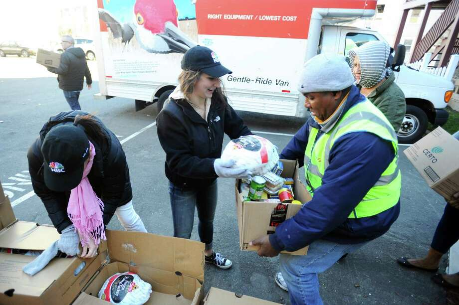 Volunteer Becca Valente hands out a turkey during Inspirica's Thanksgiving turkey giveaway at the Inspirica Woodland Center in Stamford, Conn. on Tuesday, Nov. 22, 2016. Photo: Michael Cummo / Hearst Connecticut Media / Stamford Advocate