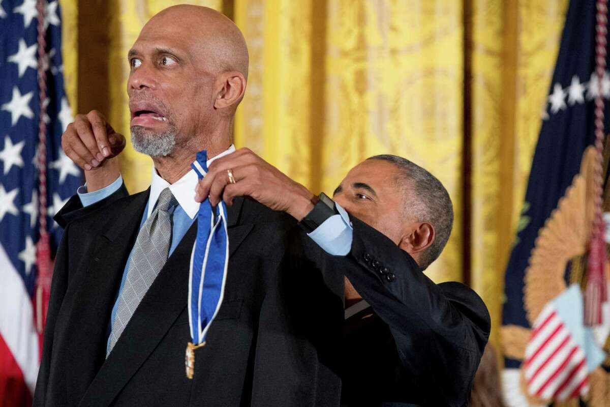 Former NBA basketball player Kareem Abdul Jabbar, left, reacts as President Barack Obama, right, attempts to present the Presidential Medal of Freedom during a ceremony in the East Room of the White House, Tuesday, Nov. 22, 2016, in Washington.