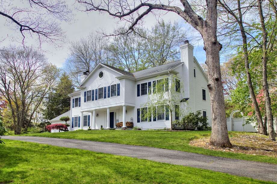 The white clapboard colonial house with forest green shutters at 93 Newtown Turnpike sits on a two-acre level property that is walking distance to The Country Store and Deli and the Merritt Parkway.