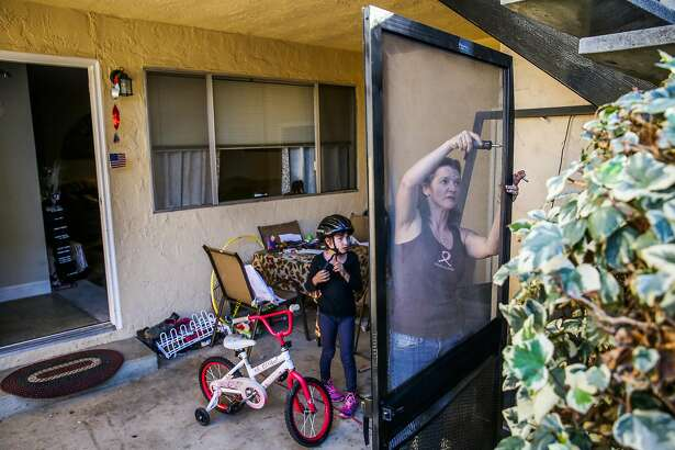 Andrea Johnson (right) fixes a screen door while her daughter Amber Phillips, 8, plays on her bike outside their apartment, in San Jose, California, on Thursday, Nov. 17, 2016. Andrea and her daughter Amber and son Joey lived in their R.V. for 9 months before getting permanent housing.