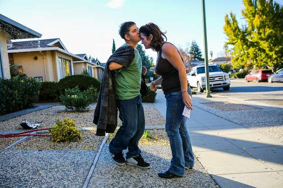 Jose Francisco Alvarez (left), 12, gives a kiss to his mother Andrea Johnson, after arriving home from school, in San Jose, California, on Thursday, Nov. 17, 2016. Jose, otherwise known as Joey, has autism and goes to a school in Palo Alto that is able to attend to his needs. Andrea and her daughter Amber and son Joey lived in their R.V. for 9 months before getting permanent housing.