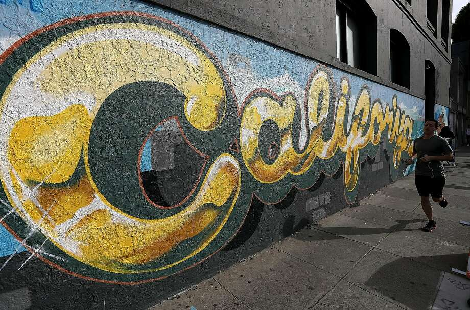 A jogger runs by a mural in San Francisco that blatantly boosts California, arguably the most powerful of the 50 states. Photo: Justin Sullivan, Getty Images