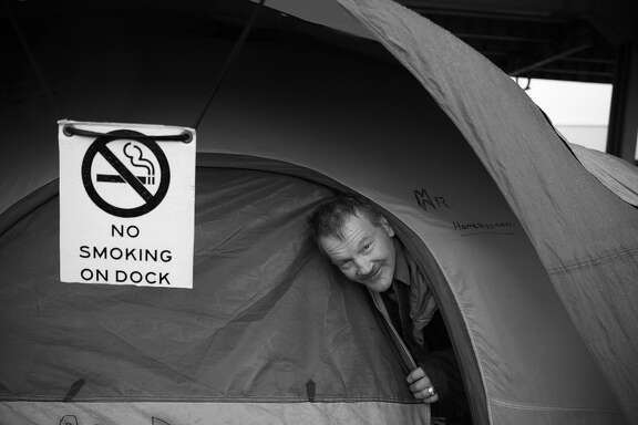 Oscar McKinney peeks out of his tent on 13th Street after a visit from the San Francisco Homeless Outreach Team on Friday, January 22, 2016 in San Francisco, Calif.