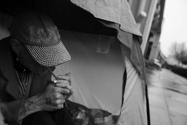 Kathy Gray lights her cigarette as she takes shelter from the rain while sitting at the entrance to her tent along 13th Street on Friday, January 22, 2016 in San Francisco, Calif.