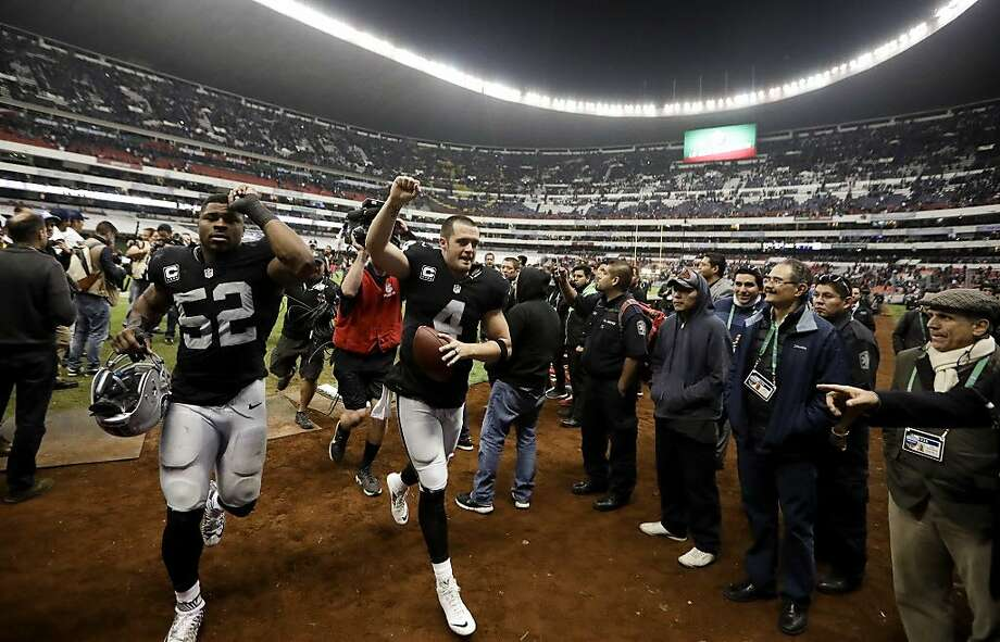 Oakland Raiders quarterback Derek Carr, center, and defensive end Khalil Mack (52) celebrate after their NFL football game against the Houston Texans Monday, Nov. 21, 2016, in Mexico City. The Raiders won, 27-20. (AP Photo/Eduardo Verdugo) Photo: Eduardo Verdugo, Associated Press