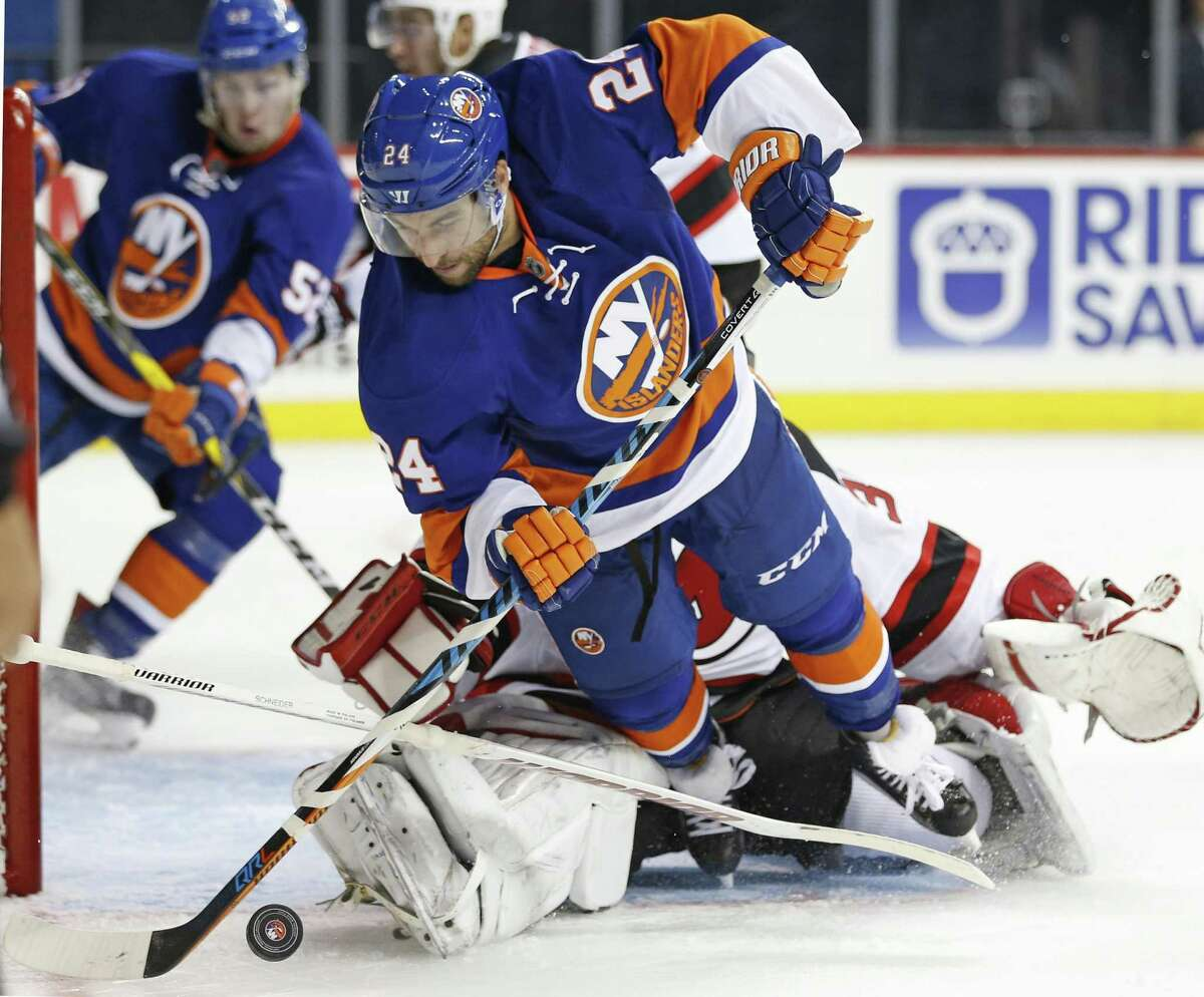 The Islanders' Stephen Gionta (24) trips over Devils goalie Cory Schneider during the second period of a preseason hockey game on Oct. 3.