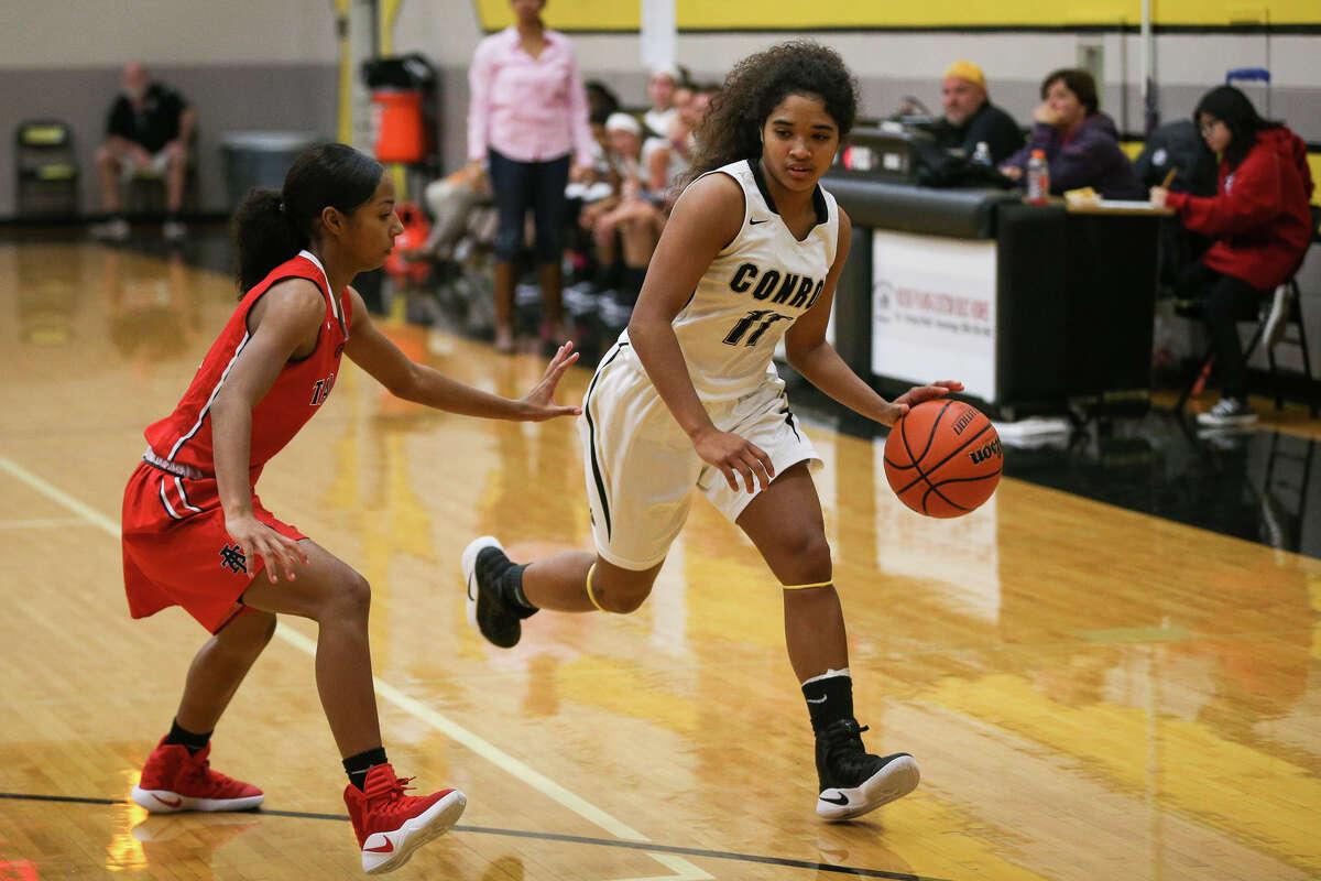 Conroe's Jznae Kim (11) drives for the basket as Katy Taylor's Alianna Garza (2) defends during the varsity girls basketball game on Tuesday, Nov. 22, 2016, at Conroe High School. (Michael Minasi / Chronicle)
