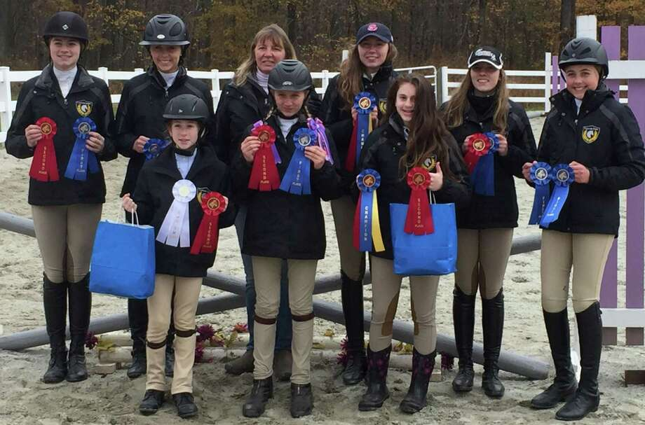 Cavalier Farm in New Milford has announced its middle and high school interscholastic equestrian teams each won champion at their first show of the season. The show was held Nov. 5 at ABF Equine in Coventry. They are, from left to right, in front, Reagan Rivera, Devon LeMoine and Madison Jennes and, in back, Annie Fournier, Alycia Petrauskas, coach Cheryl LeMoine, Chelsea LeMoine, Jordan Guilmart and Carolynn DeBellis. Photo: Courtesy Of Cavalier Farm