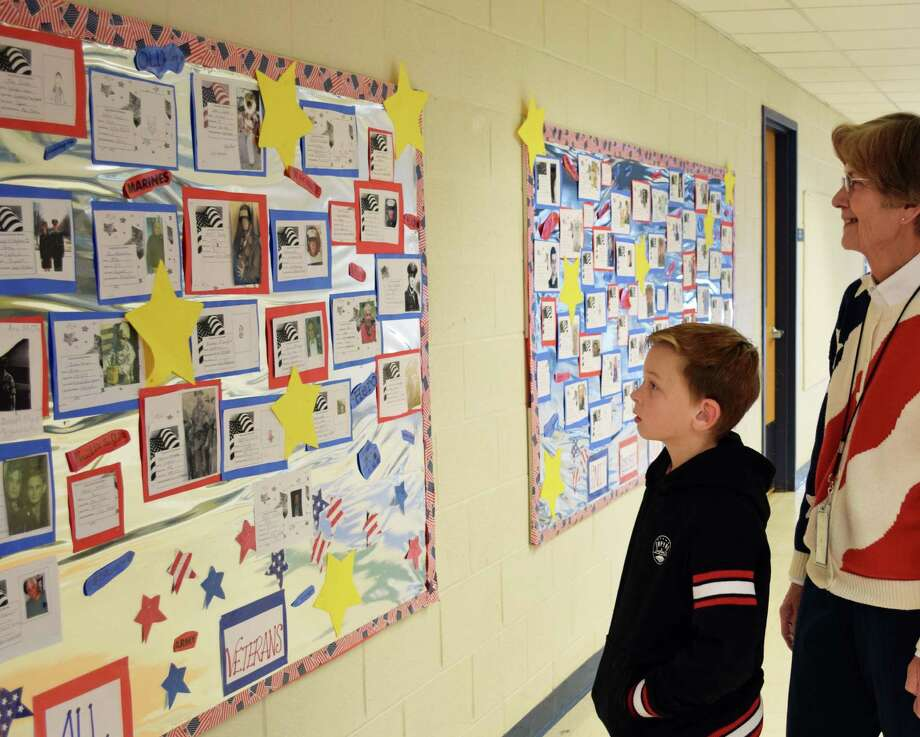 Spectrum/Sarah Noble Intermediate School sub Joy Gaiser and fifth-grade student Everett Wilkinson admire the school's bulletin board adorned with information about students' family and friends who are veterans. November 2016 Photo: Deborah Rose / Hearst Connecticut Media / The News-Times  / Spectrum