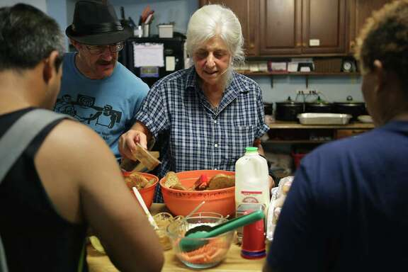 Chris Plauche, director of the Catholic Worker House, assists homeless clients with food on Wednesday, Nov. 2.